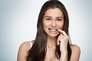 A woman with metal braces suffering from cavities!