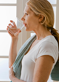 A woman drinking a glass of tap water.