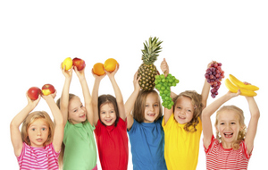 Several kids holding up healthy dental friendly foods.